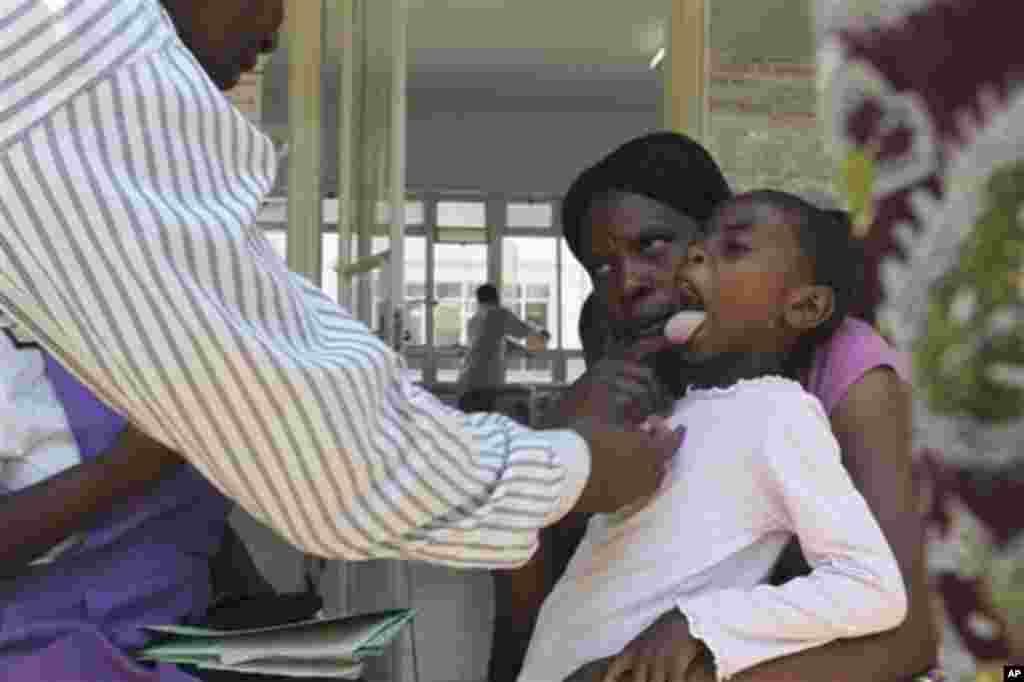A doctor examins a child suffering from typhoid at a local infectious disease hospital in Harare, Tuesday, Nov.15, 2011. Health authorities say 207 cases of typhoid, spread by contaminated water and food, are being treated in Zimbabwe's capital after a pr