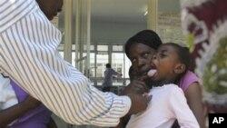 Un docteur examine un enfant suffrant de la typhoïde à Harare, le 15 novembre 2011.