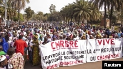 Women hold banners urging national talks to end the political paralysis in the south of Mali, in the capital Bamako, January 10, 2013.
