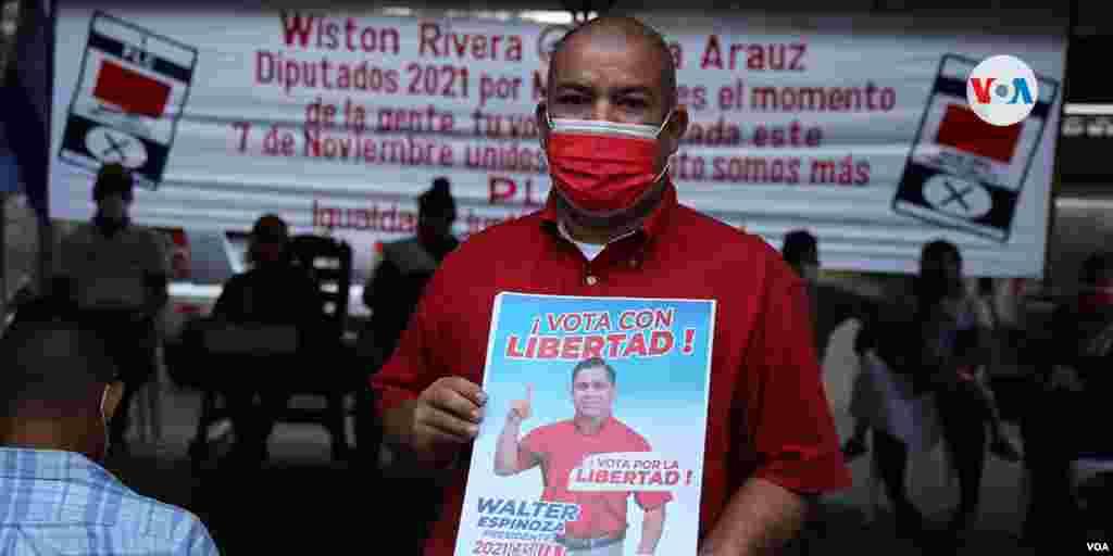 Un simpatizante del PLC muestra un cartel de apoyo al candidato Walter Espinoza.