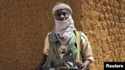 A fighter with the Tuareg separatist group MNLA (National Movement for the Liberation of Azawad) stands guard outside the local regional assembly, where members of the rebel group met with the Malian army, the UN mission in Mali and French army officers,
