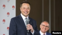 South Australian Premier Jay Weatherill, right, listens to Tesla Chief Executive Officer Elon Musk speak during an official ceremony in Adelaide, Australia, July 7, 2017. to announce that Tesla will install the world's largest grid-scale battery in the South Australian state.