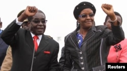 FILE - Zimbabwean President Robert Mugabe and his wife Grace wave to supporters and guests during celebrations to mark his 90th birthday in Marondera about 80km (50 miles) east of the capital Harare, Feb. 23, 2014. Mugabe turned 90 on February 21. RE