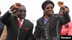 FILE - Zimbabwean President Robert Mugabe and his wife Grace wave to supporters and guests during celebrations to mark his 90th birthday in Marondera about 80km (50 miles) east of the capital Harare, Feb. 23, 2014. Mugabe turned 90 on February 21. (File Photo)