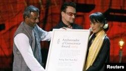 Aung San Suu Kyi (kanan) saat menerima penghargaan HAM dari Amnesty International di Dublin, Irlandia, didampingi penyanyi Bono (18/6).