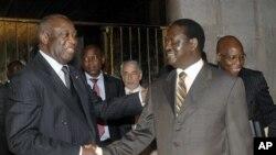 Shugaban kasa Ivory Coast Laurent Gbagbo, a hagu, yana shan hanud a Pirai Ministan kasay Kenya Raila Odinga, manzon Kungiyar Hadin kan Afrika a rudamin siyasar Ivory Coast, 17 Jan 2011.