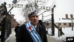 """2015年1月27日,波蘭奧斯威辛集中營的一位生還者在當年被納粹處決猶太人的""""死牆""""悼念那些遇難者之後走出紀念園大門。"""