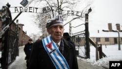 """2014年1月27日,波兰奥斯威辛集中营的一位幸存者在当年被纳粹处决犹太人的""""死墙""""悼念那些遇难者之后走出纪念园大门。"""