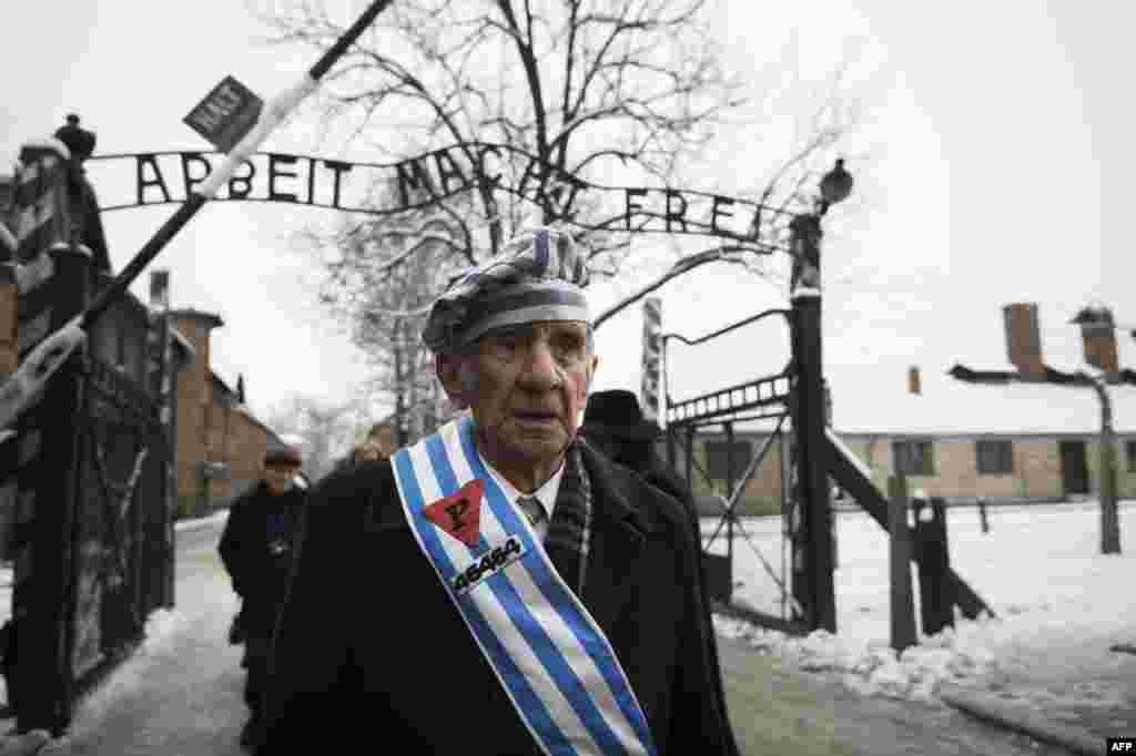 "Auschwitz survivor Miroslaw Celka walks out the gate with the sign saying ""Work makes you free"" after paying tribute to fallen comrades at the ""death wall"" execution spot in the former Auschwitz concentration camp in Oswiecim, Poland, on the 70th annivers"