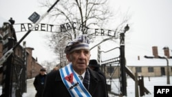 "Auschwitz survivor Miroslaw Celka walks out the gate with the sign saying ""Work makes you free"" after paying tribute to fallen comrades at the ""death wall"" execution spot in the former Auschwitz concentration camp in Oswiecim, Poland, Jan. 27, 2014."
