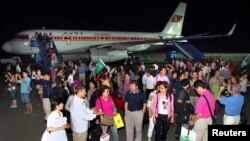 FILE - A group of tourists from Shanghai, China, arrive at an airport in Pyongyang.