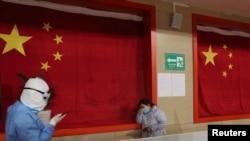 2020年2月27日,武汉一座体育馆改建的医院,一名医护人员试图安抚病患