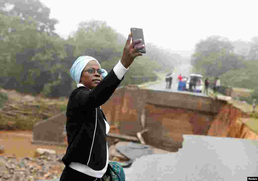 A woman takes a selfie at a washed away bridge along Umvumvu river after Cyclone Idai swept through Chimanimani, Zimbabwe, March 18, 2019.