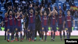 Barcelona's Gerard Pique and teammates applaud the fans at the end of the club's soccer match with Real Madrid in Madrid, Dec. 23, 2017.