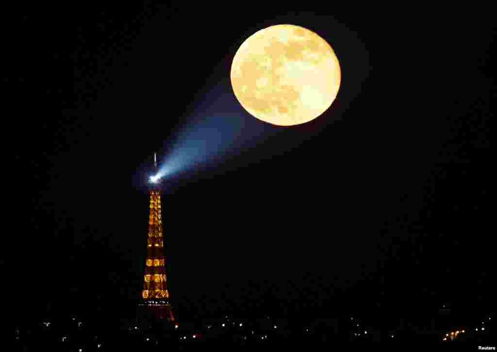 "The full moon, known as the ""Super Pink Moon"" rises behind the Eiffel Tower in Paris, France, April 27, 2021."