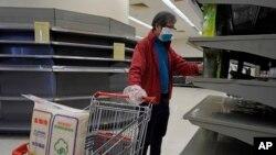 Seorang pria yang mengenakan masker dan tas plastik sebagai sarung tangan berjalan melewati rak kosong kertas tisu di sebuah supermarket di Hong Kong, Jumat, 7 Februari 2020. (Foto: AP)
