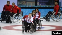 Canada's Dennis Thiessen delivers a stone during their wheelchair curling game against China at the 2014 Sochi Paralympic Winter Games, Mar. 11, 2014.