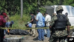 A Mexican Navy soldier watches as forensic workers remove a body and dig for others at a clandestine site that was found in the town of Tuncingo, Mexico, 03 Nov 2010