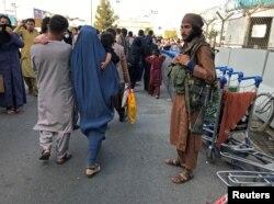 Anggota Taliban berjaga saat orang-orang berjalan di pintu masuk Bandara Internasional Hamid Karzai di Kabul, Afghanistan, 16 Agustus 2021. (REUTERS/Stringer)