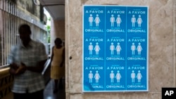 "Cuban evangelists pass beside a poster in the Evangelist League Church that reads in Spanish, ""I am in favor of the original design"" in reference to discussions on same sex marriage to be included in new constitution in Havana, Cuba, Sunday, Oct. 7, 2018. (AP Photo/Desmond Boylan)"