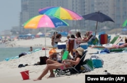In this Sunday, Aug. 1, 2010, photo, Tracy Burgess of Cullman, Ala. sits on the beach in Orange Beach, Ala.