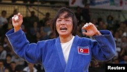 North Korea's An Kum Ae celebrates after defeating Cuba's Yanet Bermoy Acosta in their women's -52kg final judo match at the London 2012 Olympic Games July 29, 2012.