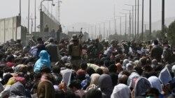 Warga Afghanistan berkumpul di pinggir jalan dekat bagian militer bandara di Kabul, 20 Agustus 2021, berharap dapat melarikan diri dari negara itu setelah militer Taliban mengambil alih Afghanistan. (Foto: Wakil KOHSAR/AFP)