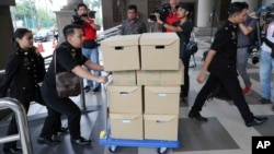 FILE - In this Wednesday, Aug. 28, 2019, file photo, Malaysian Anti-Corruption agency's staff transport documents for 1MDB case to Kuala Lumpur high court in Kuala Lumpur, Malaysia.