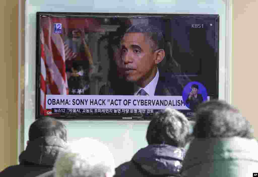 Warga menonton siaran berita televisi yang memperlihatkan Presiden AS Barack Obama di stasiun kereta api Seoul, Korea Selatan (22/12). (AP/Ahn Young-joon)