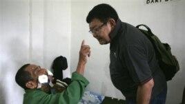 Maskut, 70, hendak memegang hidung Dr. Sanduk Ruit untuk membuktikan ia sudah bisa melihat setelah operasi mata. (AP/Binsar Bakkara)