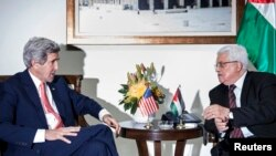 U.S. Secretary of State John Kerry (L) and Palestinian president Mahmoud Abbas talk before a meeting at the presidential compound in the West Bank city of Ramallah on January 3, 2014.