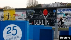 "A sign, which reads ""25 years Fall of the Wall 2014,"" is pictured in front of sections at the East Side Gallery, the largest remaining part of the former Berlin Wall in Berlin, Nov. 3, 2014."
