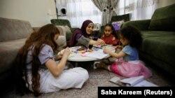 Ibu tunggal Irak Marwa Raed Taha, duduk bersama putrinya dan anak-anak kerabatnya di rumahnya, di Baghdad, Irak, 9 Mei 2021. (Foto: REUTERS/Saba Kareem)