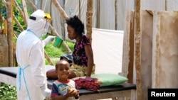 在塞拉利昂的治疗中心,全身包裹防护服的卫生人员给埃博拉病人送水