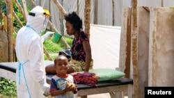 Un agent de santé, portant des vêtements de protection de la tête aux pieds, offre de l'eau à une femme atteinte du virus Ebola, dans un centre de traitement pour les personnes infectées en Sierra Leone, le 20 août 2014.