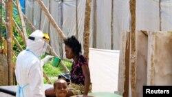 20일 시에라 리온에서 의료구호요원이 보호장비를 착용하고 에볼라 환자에게 물을 권하고 있다