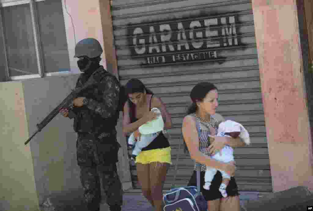 Women carring their babies walk past a soldier during an operation at the Rocinha slum, in Rio de Janeiro, Brazil. More than 1,000 police and soldiers are searching Rio's largest slum for weapons and ammunition amid a crackdown on drug gangs.
