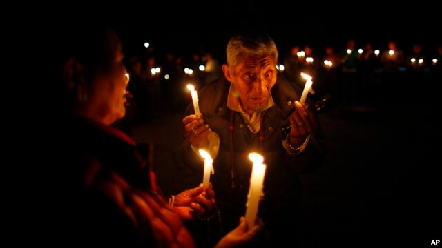 An elderly exile Tibetan participates in a candle-lit vigil in solidarity with fellow Tibetans who have self immolated, in Katmandu, Nepal, Feb. 13, 2013.