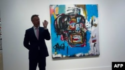"A Sotheby's official speaks about ""Untitled,"" a 1982 painting by Jean-Michel Basquiat during a media preview at Sotheby's in New York, May 5, 2017. The work sold for $110.5 million Thursday in New York, setting a new auction record for the US artist in So"