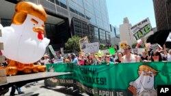 Un inflable gigante en forma de gallina, es llevado por los manifestantes que protestan contra el fracaso del presidente Donald Trump en publicar sus declaraciones en el centro de Los Ángeles el sábado 15 de abril de 2017.