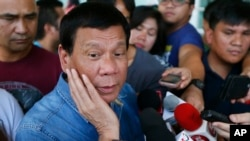 FILE - Philippine presidential candidate Rodrigo Duterte talks to the media before boarding his flight for his hometown of Davao city in southern Philippines.