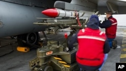 French Navy ordnance crew load a Mica missile under the wing of a Rafale fighter jet aboard France's flagship Charles de Gaulle aircraft carrier, March 25, 2011