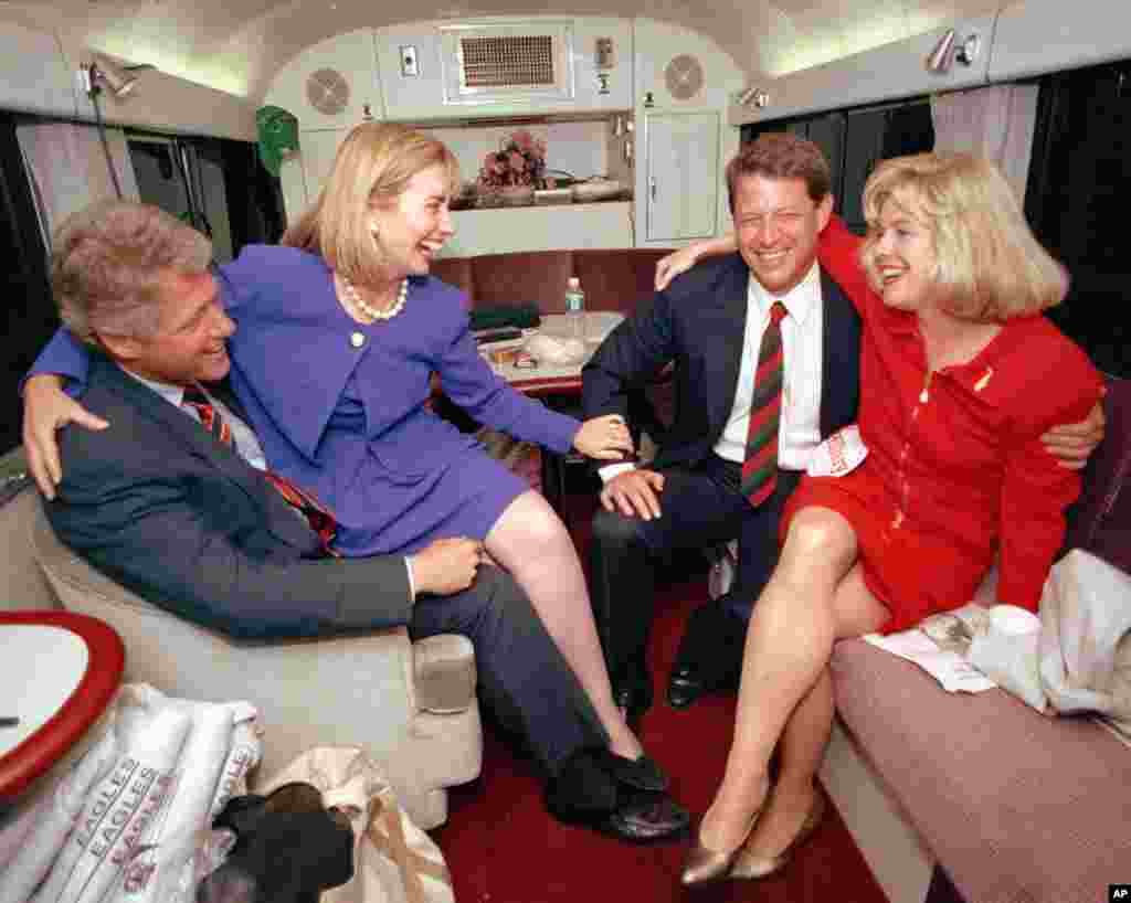 Hillary Rodham Clinton sits on the lap of her husband, democratic presidential candidate Bill Clinton left, as she jokes with vice presidential candidate Al Gore and his wife, Tipper, during a brief rest on their bus in Durham, N.C., Monday, Oct. 26, 1992