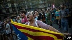 ស្ត្រីម្នាក់កាន់ទង់ជាតិ Catalan ខណដែលបាតុករហែរក្បួននៅក្នុងទីក្រុង Barcelona ប្រទេសអេស្ប៉ាញកាលពីថ្ងៃពុធទី០៣ តុលា ២០១៧។