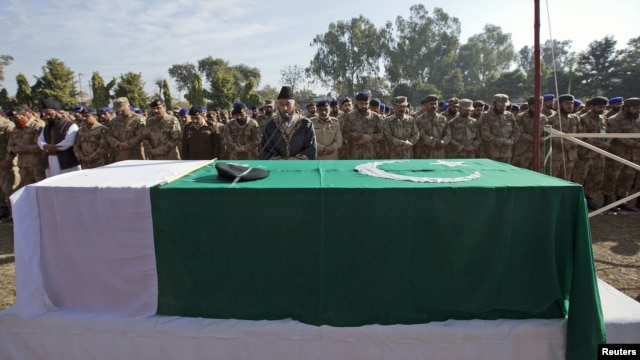 Soldiers stand near the flag-draped casket of their colleague Havildar Ghulam Mohyuddin, whom the Pakistan military said was killed by Indian soldiers while manning a post on the Line of Control (LoC) in the disputed region of Kashmir, during funeral prayers at a garrison mosque in Jhelum, January 11, 2013.