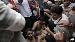 Egyptian protesters capture two of some 30 men armed with knives and sticks who attempted to storm the protesters' tent camp set up in Tahrir Square in Cairo, Egypt, July 12, 2011