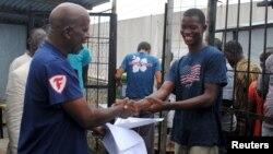 Cassius Kollie (phải), 24 tuổi, một trong bốn người được xuất viện vào hôm thứ Hai từ một đơn vị điều trị Ebola, nhận giấy chứng nhận đã khỏi bệnh ở Paynesville, Liberia, ngày 20/7/2015.