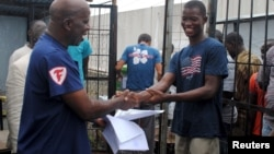 FILE - Cassius Kollie (R), 24, discharged from an Ebola treatment unit, receives a certificate for being cured of the disease in Paynesville, Liberia, July 20, 2015.