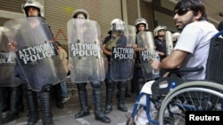 A protester in a wheelchair waits with other protesters for the troika inspectors from the European Commission, the International Monetary Fund and the European Central Bank to arrive for a meeting at the Labor ministry in Athens October 2, 2012.
