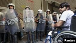 Atina'da uluslararası temsilcilerle görüşmeleri protesto eden bir engelli